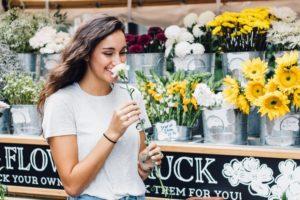 Szczęśliwa kobieta trzymająca kwiatek.