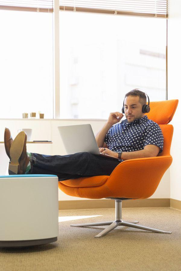 Mężczyzna pracujący z laptopem na kolanach